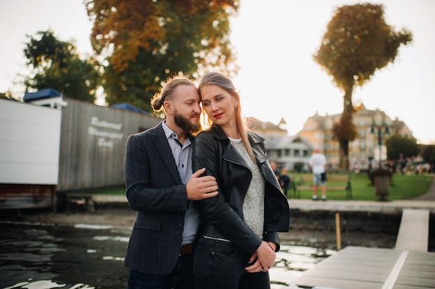 Uma família de duas pessoas fica em um píer na cidade velha da áustria ao pôr do sol. um homem e uma mulher se abraçam no aterro de uma pequena cidade na austria.europe.felden am werten ver.