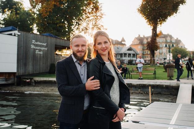 Uma família de duas pessoas fica em um píer na cidade velha da áustria, ao pôr do sol. um homem e uma mulher se abraçam no aterro de uma pequena cidade na austria.europe.