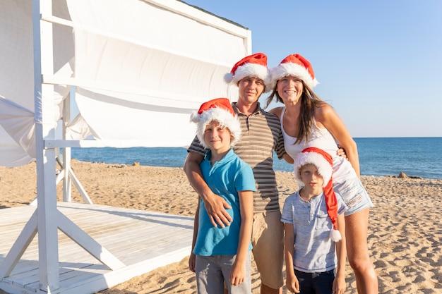 Uma família de quatro, pai mãe e dois filhos com chapéus de papai noel na praia do mar de areia. família feliz natal comemorando o ano novo à beira-mar.