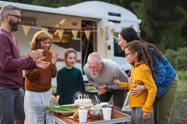 Uma família de várias gerações comemorando aniversário ao ar livre no acampamento, viagem de férias em caravana.