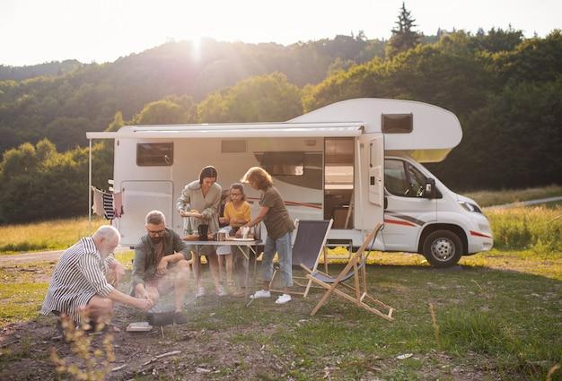 Uma família de várias gerações sentada e comendo ao ar livre de carro, viagem de férias em caravana.