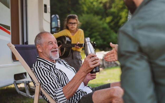 Uma família de várias gerações sentada em uma viagem de férias em caravana