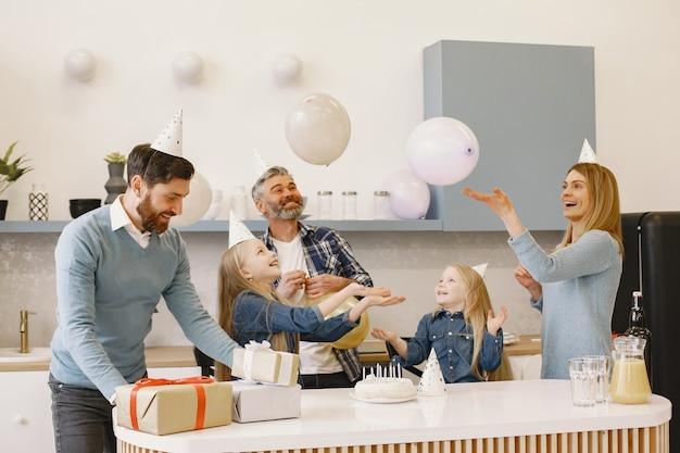 Uma família e duas filhas fazem uma festa. as pessoas têm balões. os presentes estão sobre a mesa.