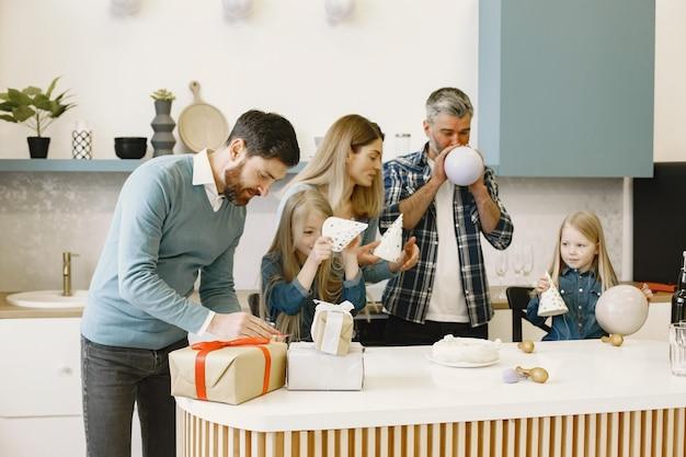 Uma família e duas filhas fazem uma festa. pessoas soprando balões. os presentes estão sobre a mesa.