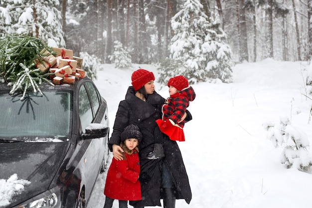 Uma família está ao lado do carro com uma árvore de natal e presentes