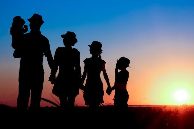 Uma família feliz à beira-mar ao pôr do sol em uma silhueta de viagens na natureza