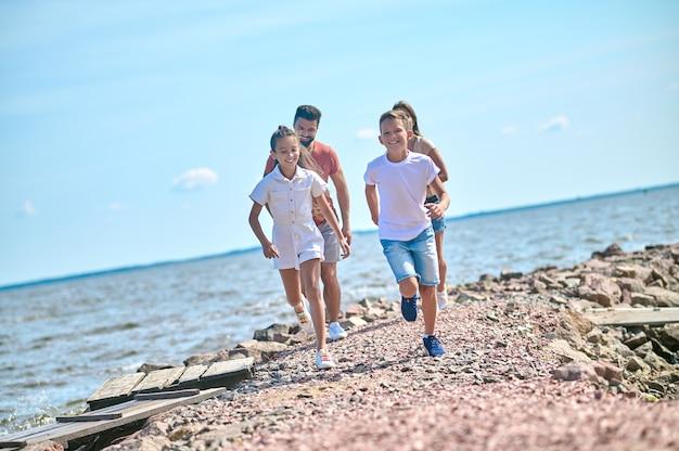 Uma família feliz, animada e correndo na praia