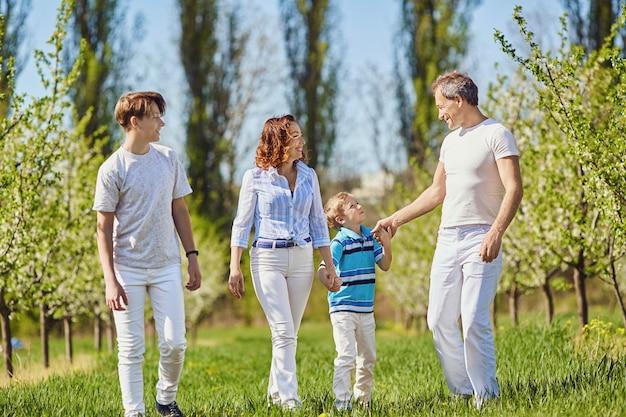 Uma família feliz caminha no jardim na primavera, no verão