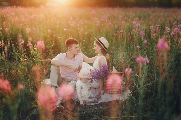 Uma família feliz caminha por um prado de flores. amor e primavera florescendo