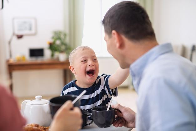 Uma família feliz com filho de síndrome de down à mesa, rindo ao tomar café da manhã.