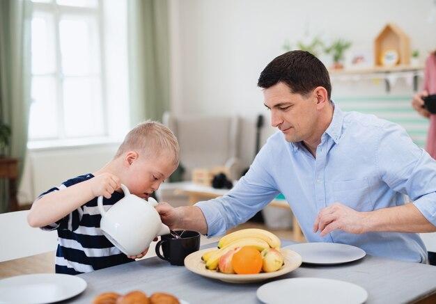 Uma família feliz com filho de síndrome de down à mesa, tomando café da manhã.