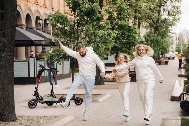 Uma família feliz com roupas brancas caminha pela cidade.