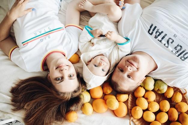 Uma família feliz de três frutas diferentes, deita-se no sofá e aproveita a vida juntos