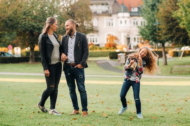 Uma família feliz de três pessoas corre pela grama na cidade velha da áustria. uma família caminha por uma pequena cidade na áustria. europa. velden am werten zee.