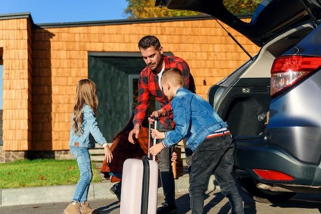 Uma família feliz desempacota bagagens do porta-malas de um carro depois de se mudar para uma nova casa.
