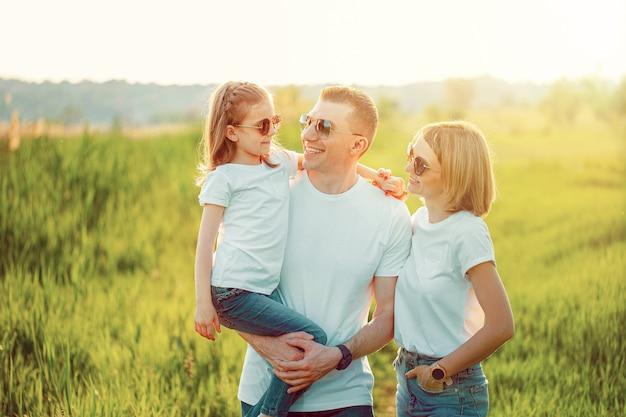 Uma família feliz em camisetas brancas, óculos escuros e jeans no parque