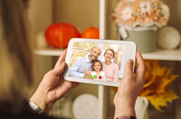Uma família feliz está cumprimentando seus pais em uma videoconferência
