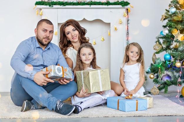 Uma família feliz está sentada no tapete junto à lareira branca com uma elegante árvore de natal