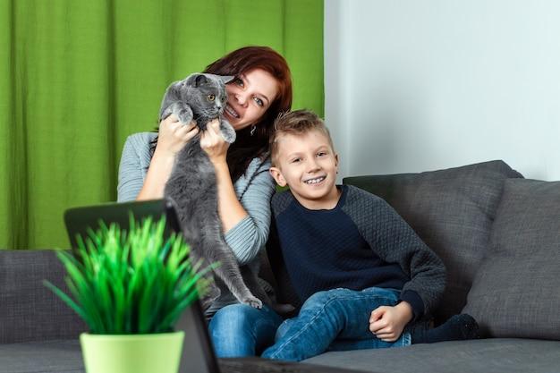 Uma família feliz, mãe, filho e gato estão sentados no sofá sentindo feliz