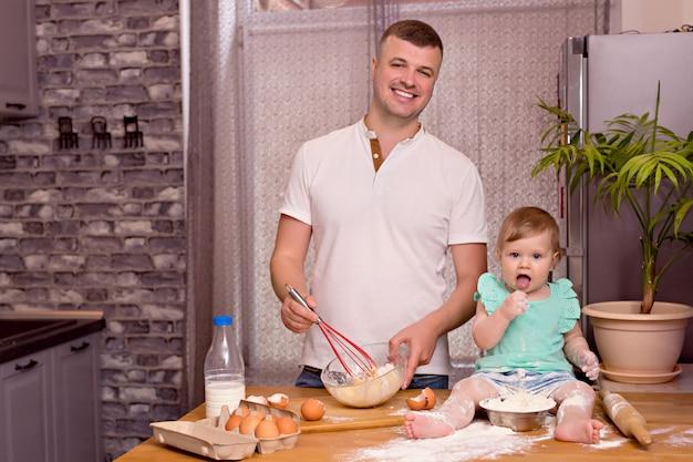 Uma família feliz, pai, filha brincam e cozinham na cozinha, amassam a massa e assam biscoitos.