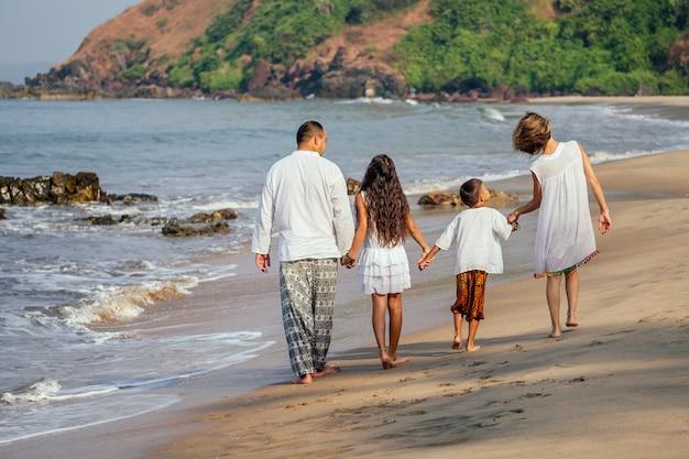 Uma família forte caminha pela praia na parte de trás
