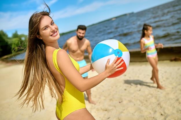 Uma família jogando vôlei de praia e se sentindo feliz