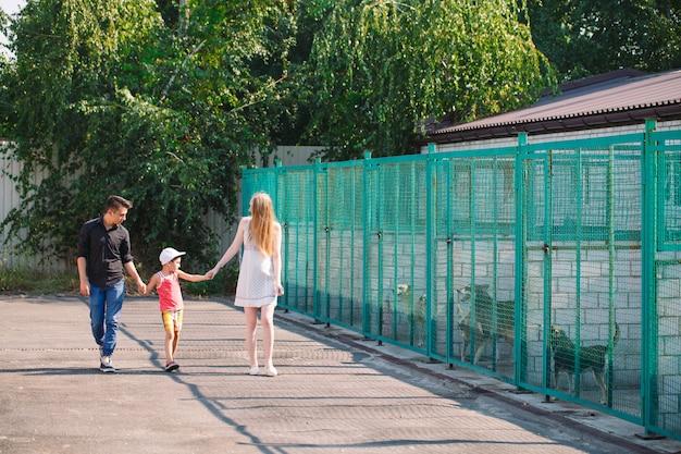 Uma família jovem procura um animal de estimação em um abrigo para cães.