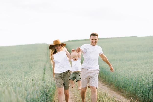 Uma família jovem se diverte com seu bebê no campo
