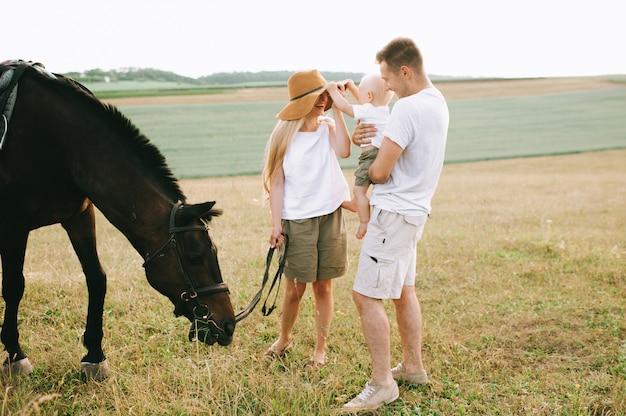 Uma família jovem se diverte no campo. pais e filho com um cavalo