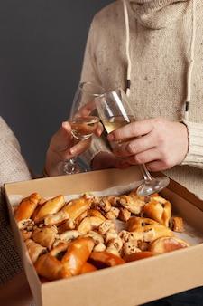 Uma família oferece taças de champanhe e uma caixa de pastéis, doces, salgadinhos