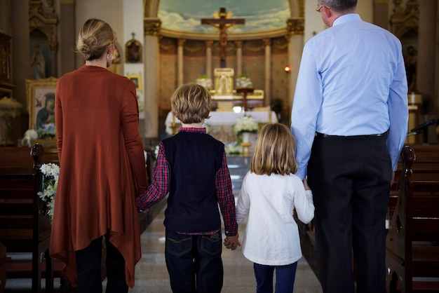 Uma família rezando juntos dentro de uma igreja