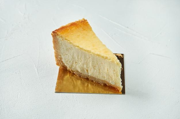 Uma fatia clássica de bolo de queijo mascarpone new york em uma superfície estrutural branca. fechar-se