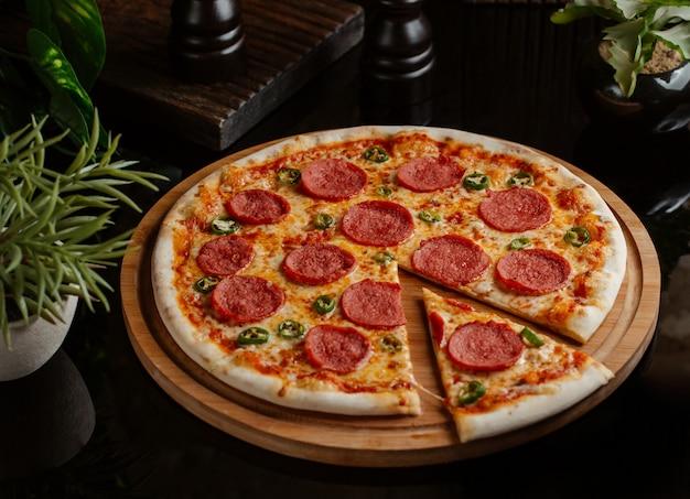 Uma fatia cortada da pizza de pepperoni clássica com rolos de pimenta verde
