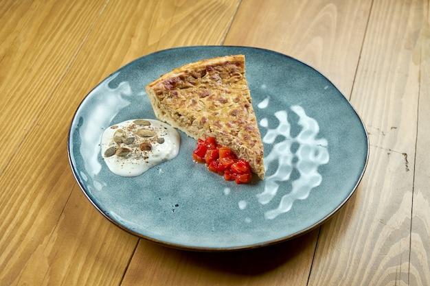 Uma fatia da clássica torta de cebola alemã com molho de tomate e molho branco. fundo de madeira.