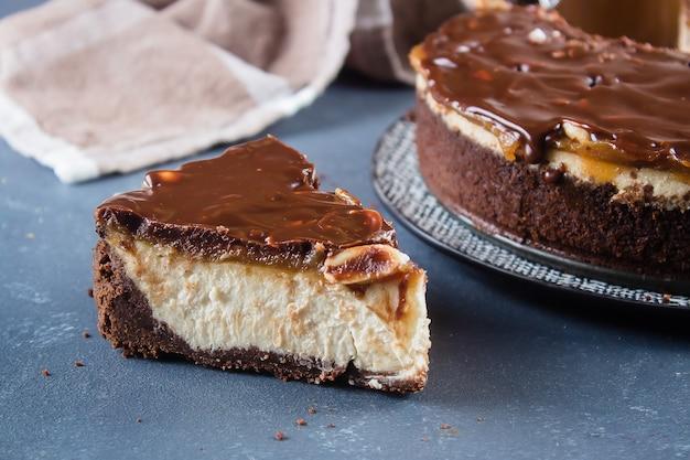 Uma fatia da parte de bolo de queijo snickers no fundo concreto azul.