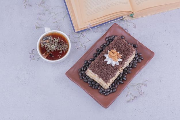 Uma fatia de bolo com chocolate picado e uma xícara de chá de ervas