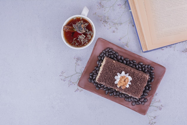 Uma fatia de bolo com chocolate picado e uma xícara de chá