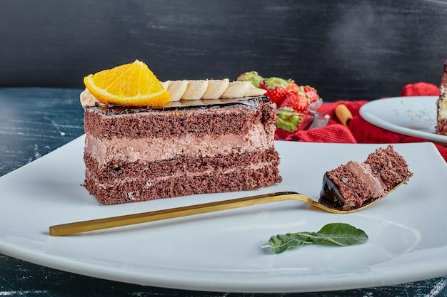 Uma fatia de bolo com creme de chocolate e frutas.