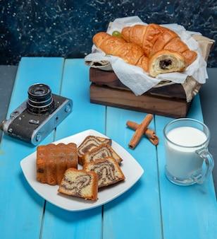 Uma fatia de bolo de baunilha com chocolate e uma xícara de chá embrulhada por uma toalha de mesa.