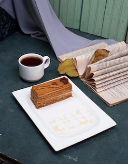 Uma fatia de bolo de cacau com uma xícara de chá.