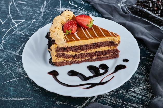 Uma fatia de bolo de caramelo com frutas vermelhas.
