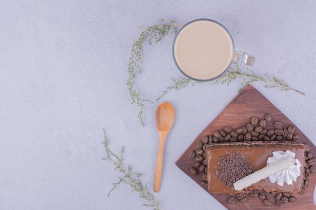 Uma fatia de bolo de caramelo com um copo de cappuccino