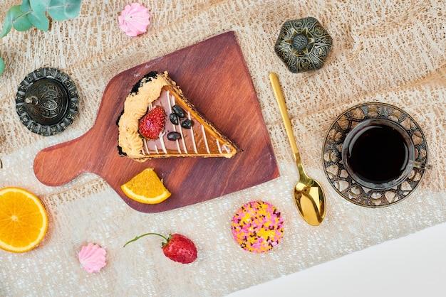 Uma fatia de bolo de caramelo de chocolate com um copo de chá, vista de cima.