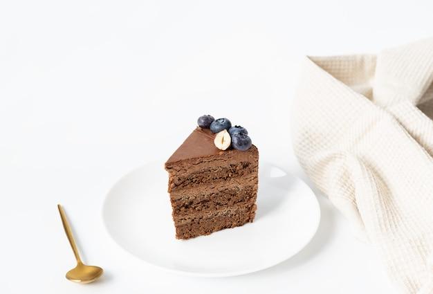 Uma fatia de bolo de chocolate caseiro com mirtilos e nozes em um prato branco sobre fundo branco