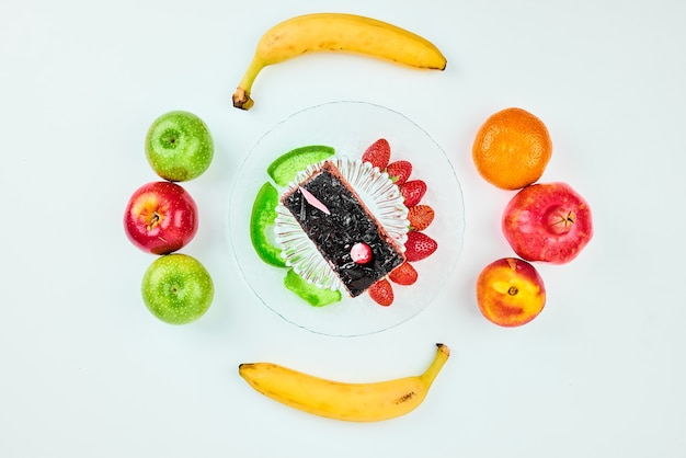Uma fatia de bolo de chocolate com composição de frutas.
