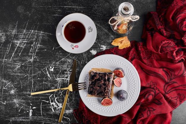 Uma fatia de bolo de chocolate com frutas e uma xícara de chá, vista de cima.