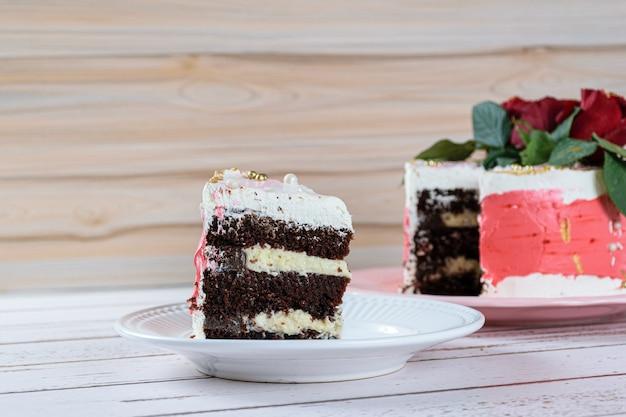 Uma fatia de bolo de chocolate com recheio de mascarpone e cobertura de creme de manteiga de merengue suíço, ao lado do bolo.