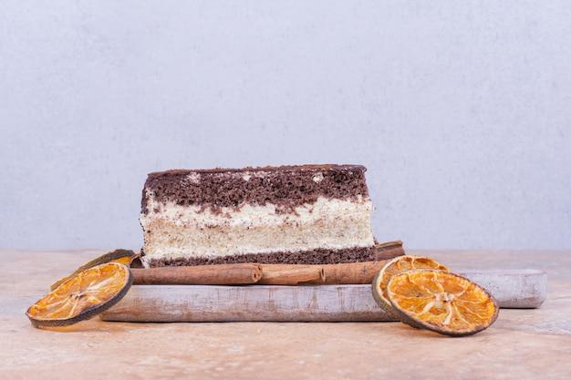 Uma fatia de bolo de chocolate com rodelas de laranja e canela