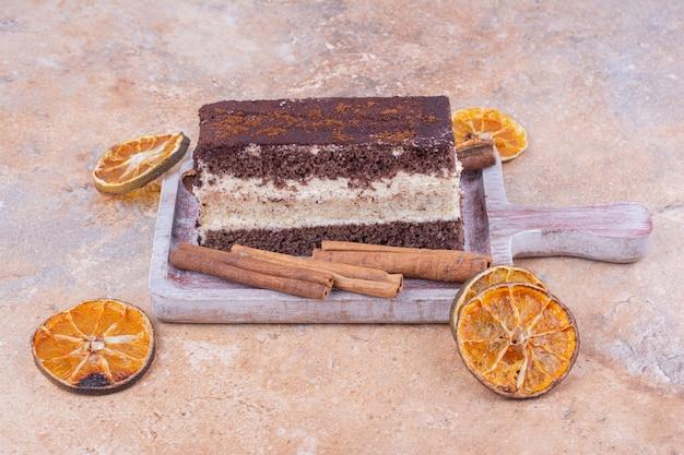 Uma fatia de bolo de chocolate com rodelas de laranja secas