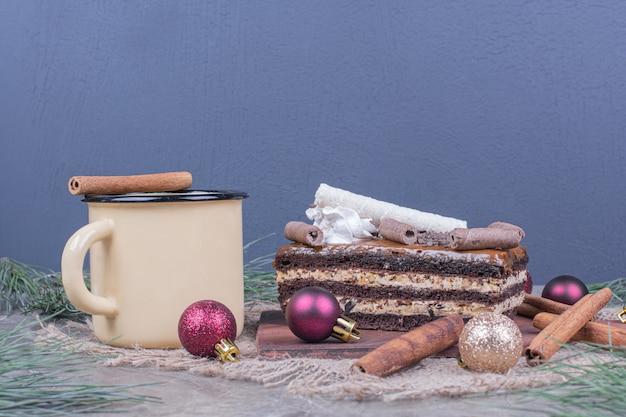 Uma fatia de bolo de chocolate com um copo de bebida e enfeites de natal ao redor